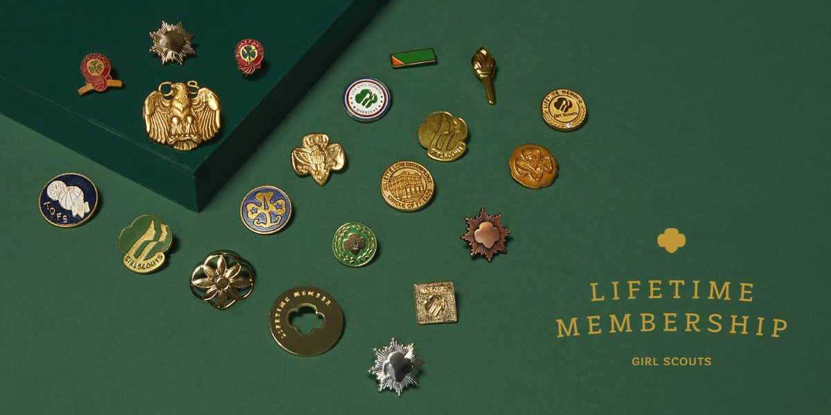 A selection of Girl Scout pins on a green background.
